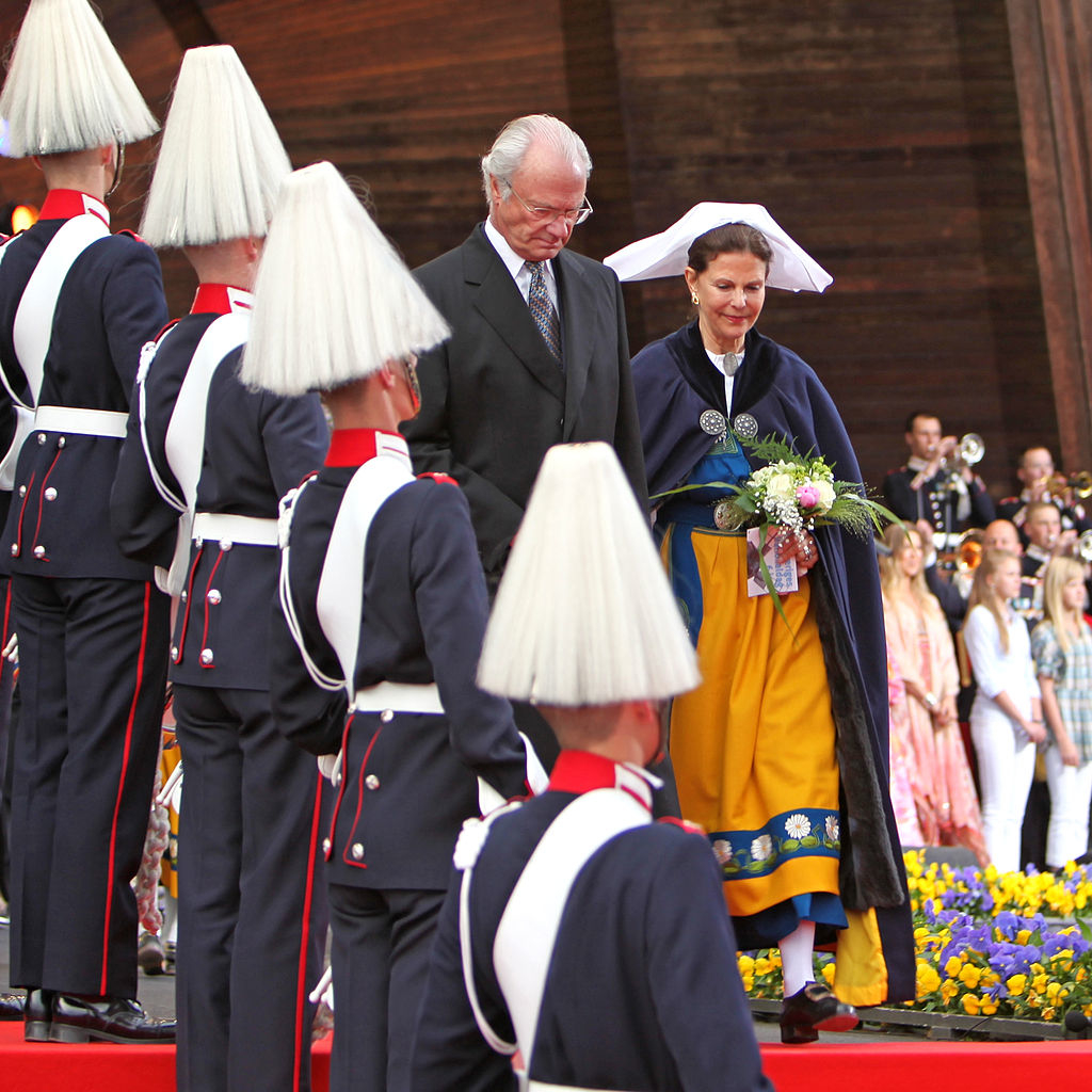 King Carl XIV Gustaf and Queen Silvia (in traditional national dress) arrive to celebrations in Skansen Park on the Swedish National Day 2009; a military band stands in attention. Photo by Bengt Nyman