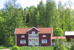 A little red cottage by the edge of the forest.